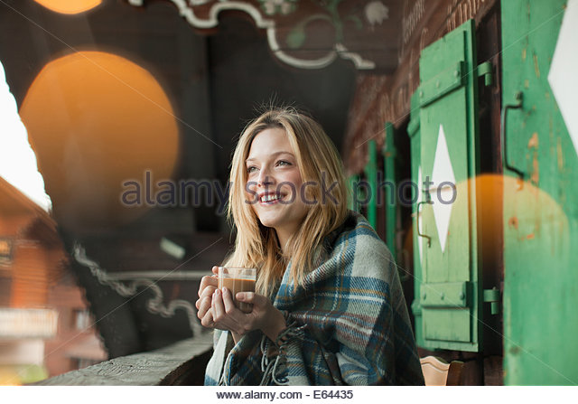 Smiling woman wrapped in a blanket and drinking coffee on cabin porch - Stock-Bilder