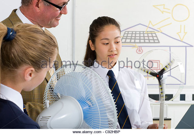 Teacher and students in school uniforms with wind turbine model in science class - Stock Image