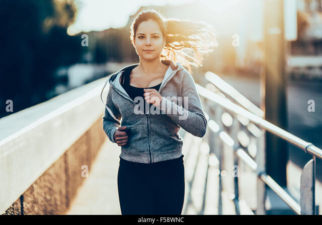 Sporty woman jogging in city to keep her body and soul in shape - Stock-Bilder