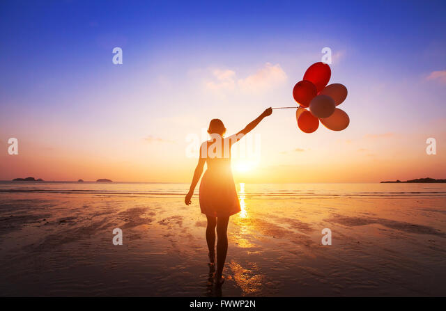 happiness concept, positive emotions, happy girl with multicolored balloons enjoying summer beach at sunset - Stock Image