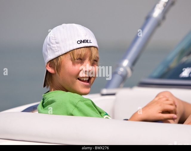 Cheeky young boy with hat reversed sat in a speed boat - Stock Image