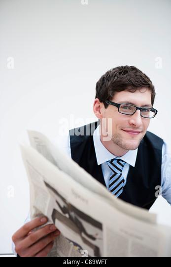 Germany, Bavaria, Diessen am Ammersee, Businessman holding newspaper, smiling, portrait - Stock-Bilder