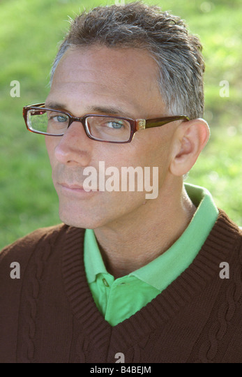 Head and Shoulders Portrait of a Gray Haired Man Wearing Horn Rimmed Eyeglasses a Green Golf Shirt and a Brown V - Stock Image