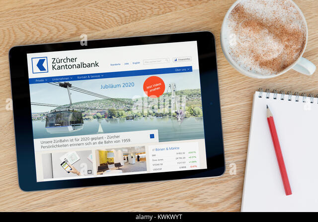 The Zurich Cantonal Bank website on an iPad tablet device, resting on a wooden table beside a notepad, pencil and - Stock Image