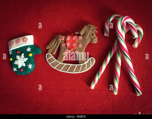 Directly Above View Of Horse Shaped Chocolate With Candy Canes On Carpet - Stock Image