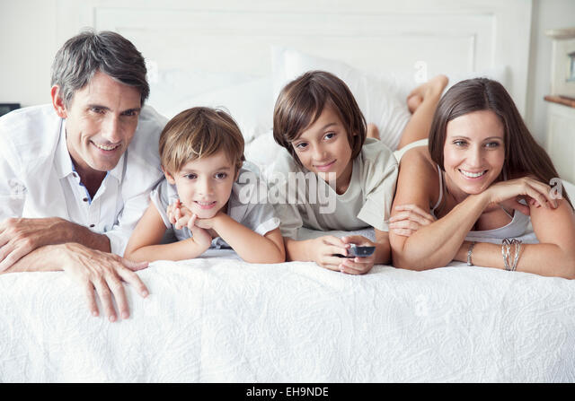 Family watching TV on bed, portrait - Stock Image
