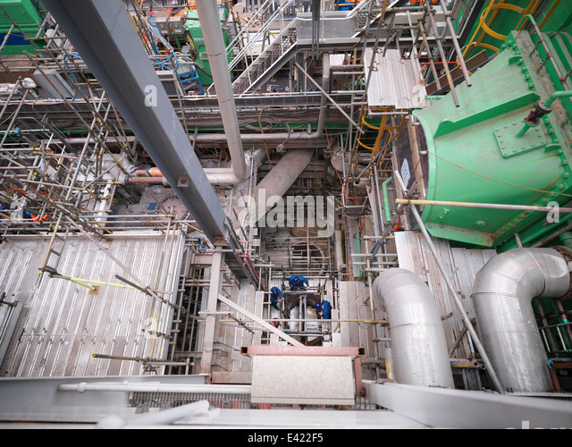 Engineers working deep down in equipment during power station outage, high angle view - Stock Image