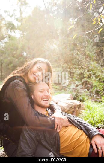 Man lying on woman's lap on rock. - Stock-Bilder