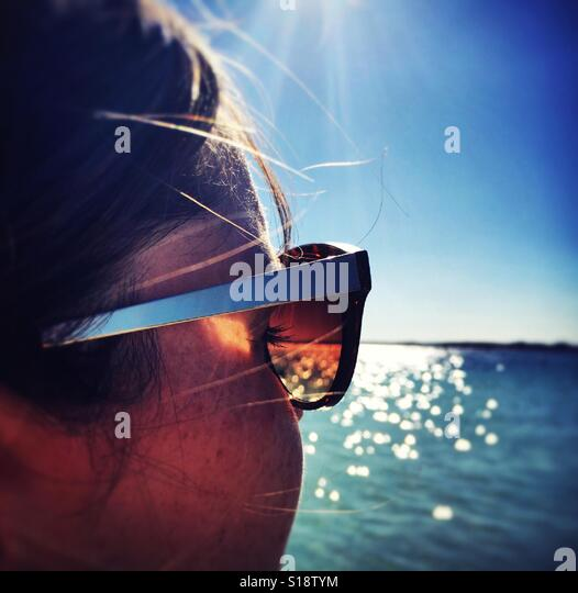 Stylish young woman by the sea - Stock-Bilder