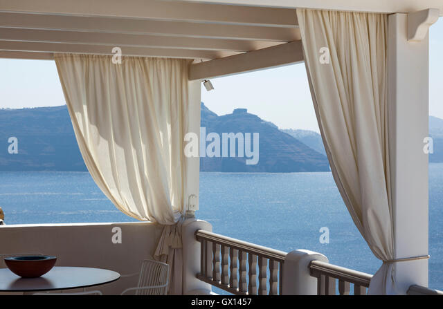 Curtained shades to protect diners against the sun in the Greek island of Santorini. The clear blue ocean is in - Stock Image