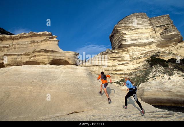 A man and woman participating in Running, Crossrunning, steep coast, Santa Manza, Bonifacio, Corsica, France, Europe - Stock Image