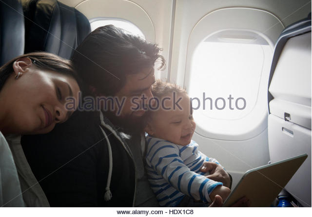 Hispanic father and son using digital tablet on airplane - Stock Image