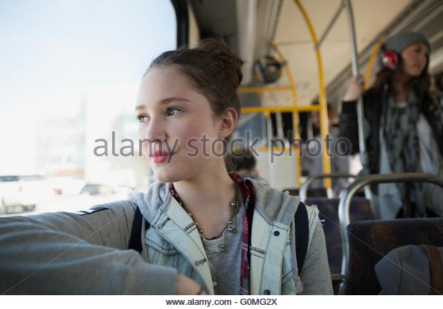 Pensive teenage girl riding bus looking out window - Stock Image