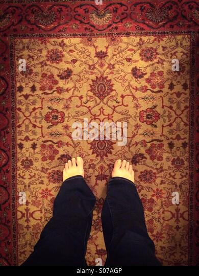 Bare feet on rug - Stock Image