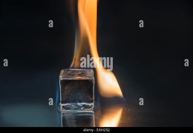Burning ice cube on a shiny surface - Stock Image