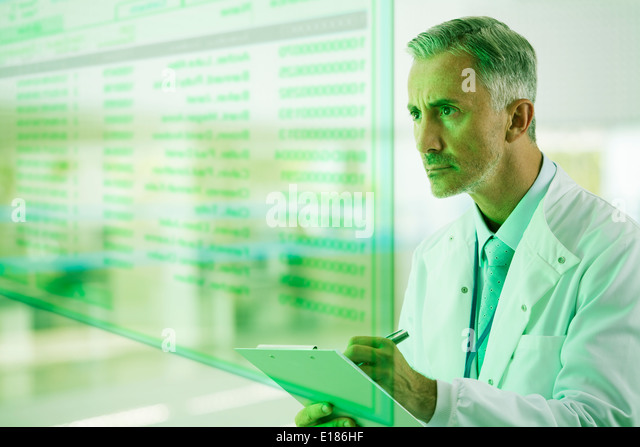 Serious doctor with clipboard - Stock Image