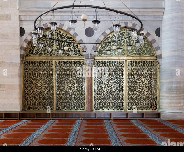 Interior shot of two arched ornate engraved golden doors, big chandelier over marble wall with pillars and red decorated - Stock Image