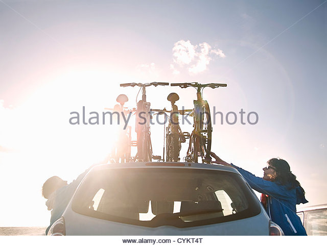 Mother and son tying bicycles on car - Stock-Bilder