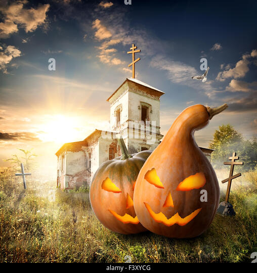 Halloween pumpkins on a churchyard near old church - Stock Image
