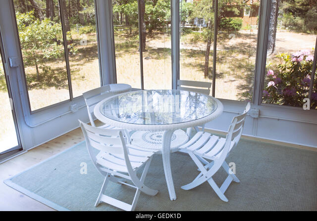 Table and chairs on a screened-in back porch on Cape Cod. - Stock Image