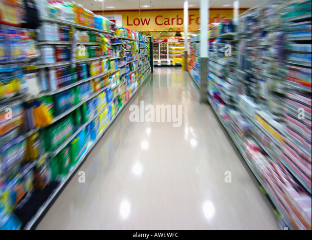 Motion Blurred Image of an Aisle in a Supermarket and Low Carb Sign on Wall No People Copy Space - Stock Image