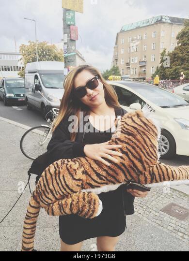 Portrait Of Woman Holding Tiger Stuffed Toy On Sidewalk - Stock Image