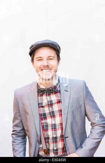 Portrait of young man wearing silver suit jacket and flat cap - Stock Image