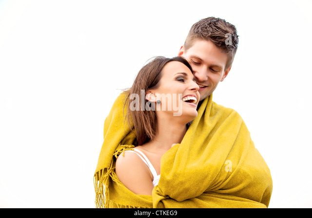 Portrait of a romantic couple embracing while wrapped with a blanket - Stock Image