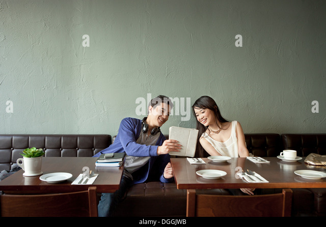 Young man showing young woman digital tablet in restaurant - Stock Image
