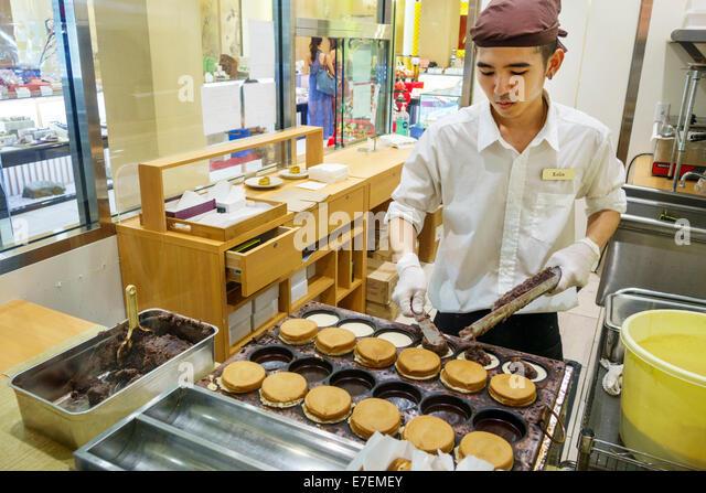 Hawaii Oahu Hawaiian Honolulu Ala Moana Center centre mall Minamoto Kitchoan sweets confections desserts Asian man - Stock Image