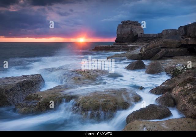 Waves break over the rocky shoreline of Portland Bill, Isle of Portland, Dorset, England. Spring (April) 2012. - Stock-Bilder