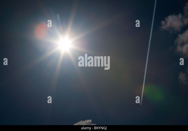 Airplane smoke trail is seen against a bright sun. - Stock Image