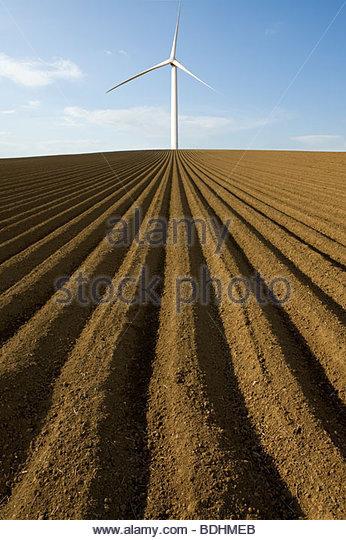 Wind turbine in ploughed field - Stock Image