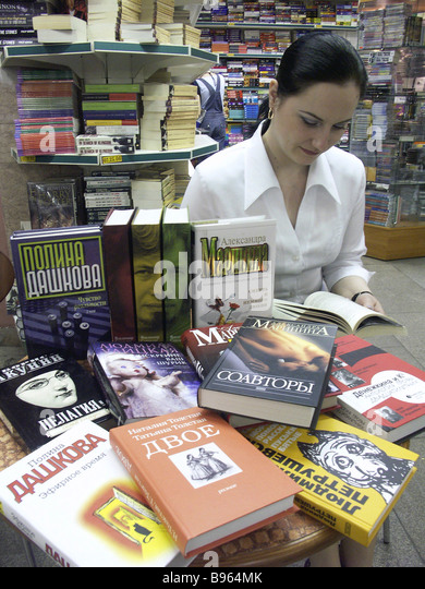 Shopper chooses book at Moscow based Biblio Globus book store - Stock Image
