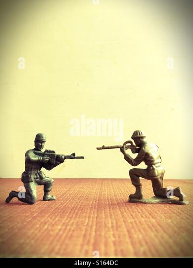 Two toy soldiers pointing guns at each other. - Stock Image
