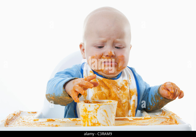 Baby boy (6- 11 Months) with baby food and crying - Stock Image