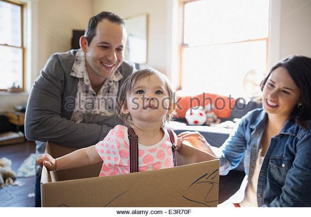Baby girl playing inside of cardboard box - Stock Image