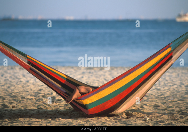 tropics tropical Beach Feet sticking out of hammock dragging on sand yucatan playa del carmen cancun area mexico - Stock Image