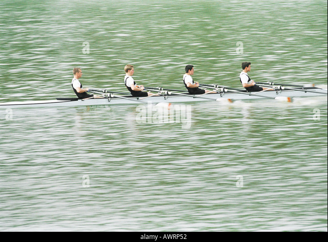Four teenage boys rowing crew in boat, side view - Stock Image
