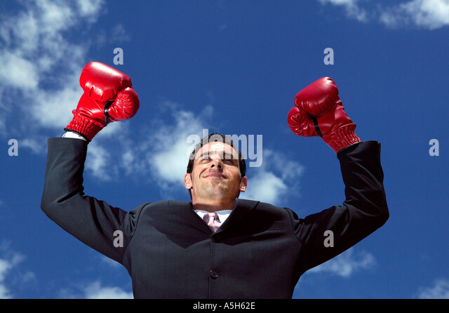 Businessman wearing boxing gloves - Stock Image