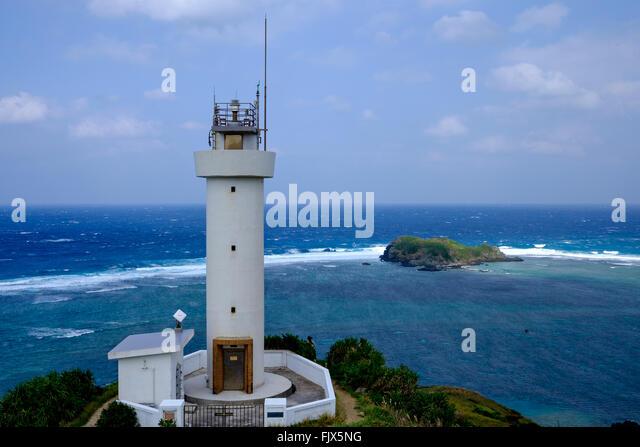 Lighthouse On Sea Against Cloudy Sky - Stock Image