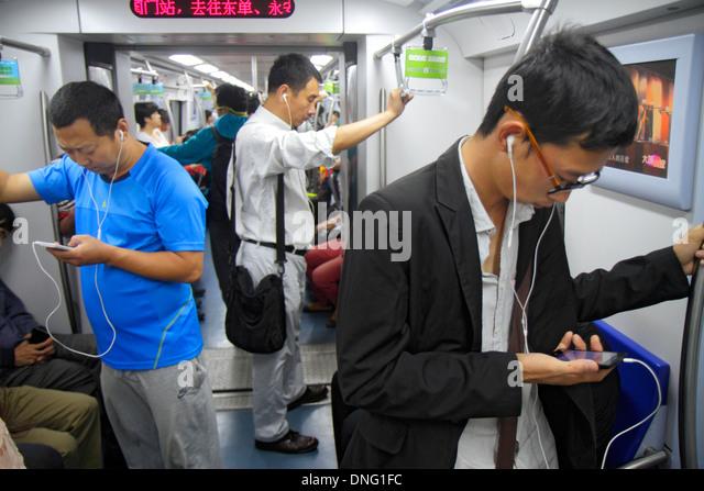 Beijing China Subway public transportation passengers riders Asian man Airport Express Train Line T3 cabin standing - Stock Image