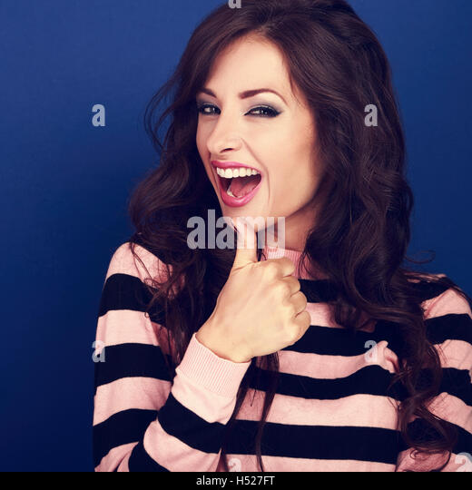 Excited smiling young woman showing thumb up sign with open mouth on blue background. Closeup portrait - Stock Image