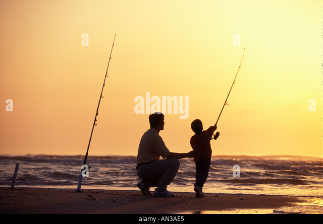 Father teaching his sonTo surf fish on the beach in North Carolina - Stock Image