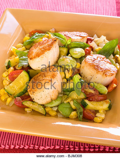 Seared Scallops with Lima Beans, Zucchini, Corn and Tomatoes - Stock Image