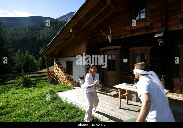 Couple playing blindman's buff beside alp lodge, Heiligenblut, Hohe Tauern National Park, Carinthia, Austria - Stock Image