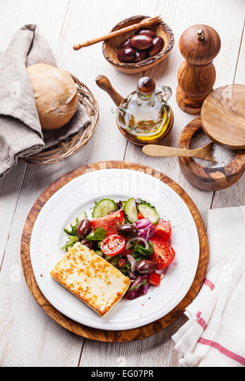 Fresh vegetable salad with grilled cheese on white wooden background - Stock Image