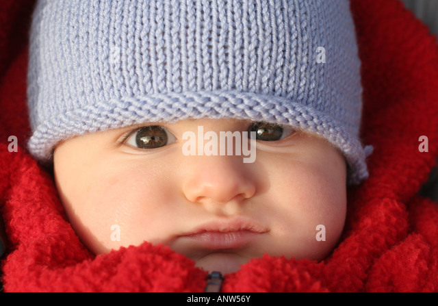 8 Month Old Baby Boy with Red Coat and Blue Woolen Hat - Stock Image