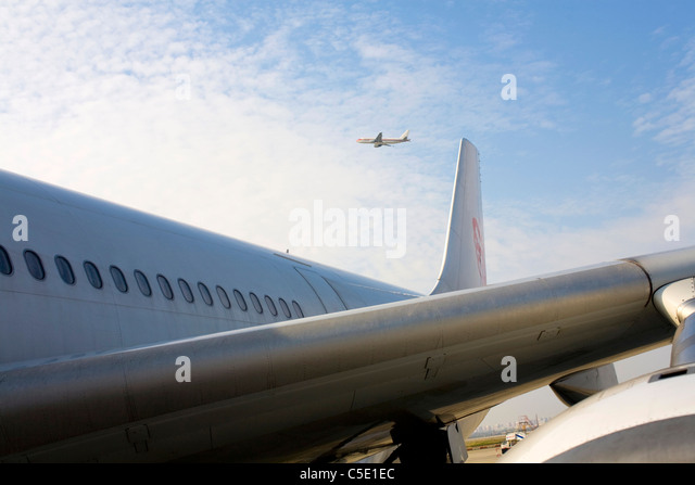 Cropped aircraft with an airplane against the blue sky and clouds - Stock Image