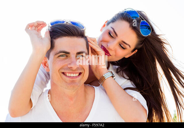 Cheerful handsome man carrying his girlfriend on his back on the beach - Stock Image